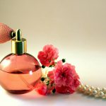 A pink bottle of perfume, next to roses. Not brand specific.
