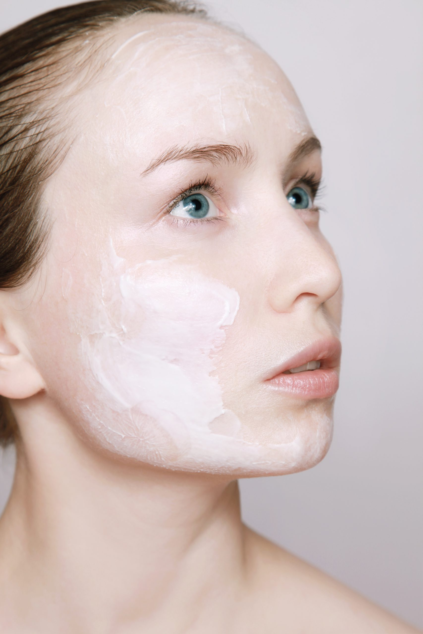 Photo of a young woman, who appears to be white, looking to the right. She has white lotion on her face.