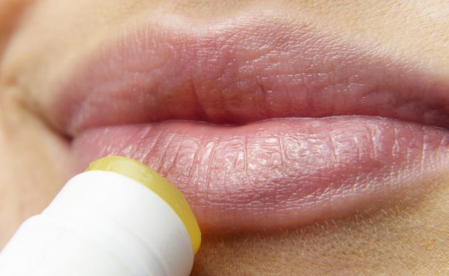 Upclose photo of lips with lip balm being applied.