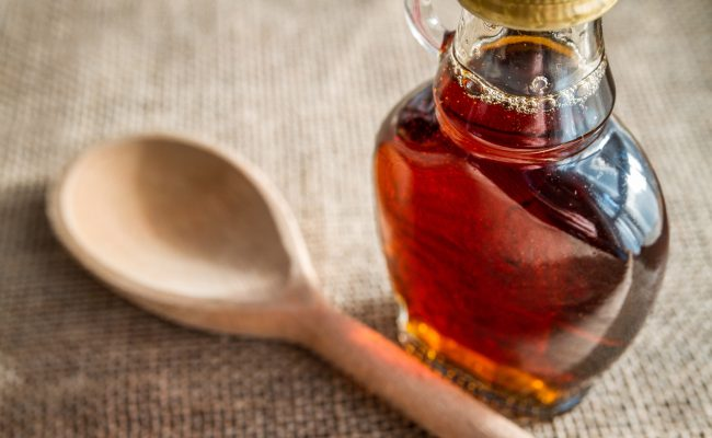 Glass jar of maple syrup next to a wooden spoon.